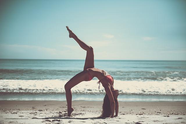 cvičící žena v plavkách na pláži – plážová jóga