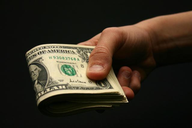 ruka nabízející větší množství bankovek