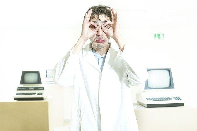 """muž hledící skrze """"brýle"""" mezi dvěma počítači."""