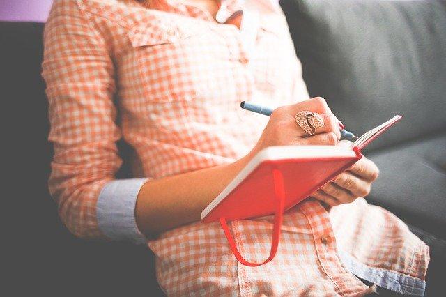 Žena píšící do deníku